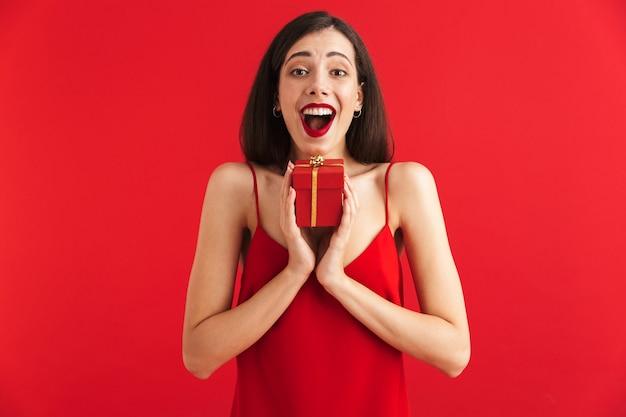 고립 된 작은 선물 상자를 들고 드레스에 쾌활 한 젊은 여자의 초상화