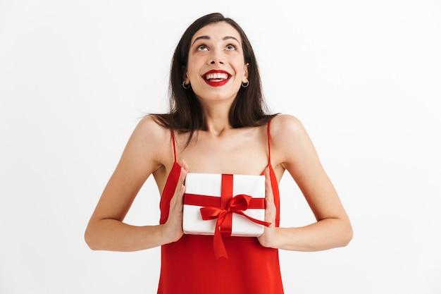 고립 된 선물 상자를 들고 빨간 드레스에 쾌활 한 젊은 여자의 초상화