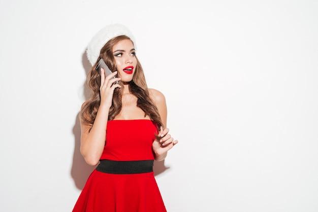 Портрет жизнерадостной молодой женщины в красном платье разговаривает по мобильному телефону и смотрит изолированно