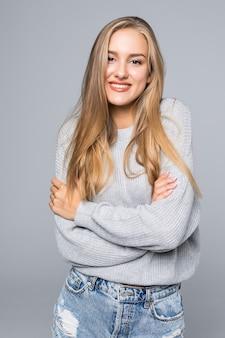 회색 배경에 넘어 팔 웃 고 스웨터에 쾌활 한 젊은 여자의 초상화