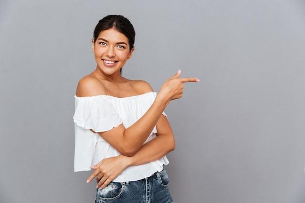 Портрет веселой молодой женщины, указывающей пальцем вдали, изолированной на серой стене