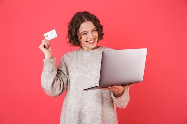 ピンクの上に孤立して立っている、ラップトップを保持し、クレジットカードを示す陽気な若い女性の肖像画