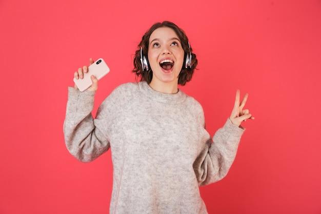 ピンクの上に孤立して立って、ヘッドフォンで音楽を聴いて、踊って陽気な若い女性の肖像画