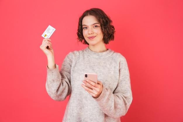 Портрет веселой молодой женщины, стоящей изолированно над розовым, используя мобильный телефон, показывая пластиковую кредитную карту
