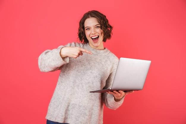 ピンクの上に孤立して立って、ラップトップコンピューターで作業している陽気な若い女性の肖像画