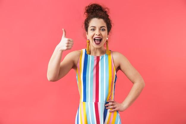 赤い背景の上に孤立して立っているドレスを着て、親指を立てる陽気な若い女性の肖像画