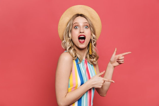 Портрет веселой молодой женщины в платье, стоящем изолированно на красном фоне,
