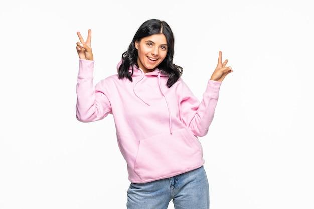 白い壁の上に孤立して立っているパーカーを着て、平和のジェスチャーを示す陽気な若い女性の肖像画