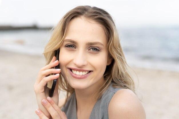 ビーチで電話で話している笑顔で陽気な若い女性の肖像画