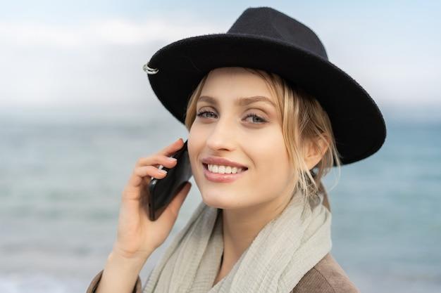 携帯電話で話し、カメラをのぞき込む完璧な笑顔で陽気な若い女性の肖像画