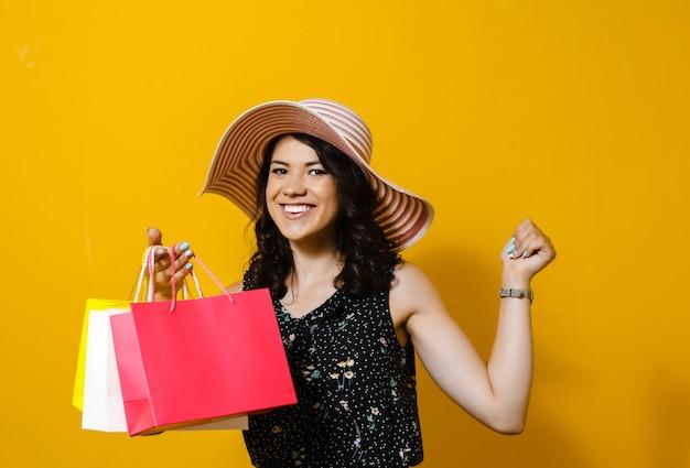 쇼핑백을 들고 모자와 쾌활 한 젊은 여자의 초상화와 노란색 벽 위에 절연 제스처를 제시