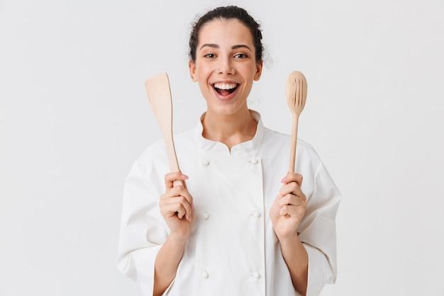 Портрет жизнерадостной молодой женщины с кухонной утварью