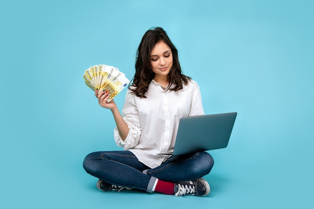 Портрет веселой красивой девушки в платье и солнцезащитных очках, держащей хозяйственные сумки и показывающей кредитную карту, изолированную на синем фоне