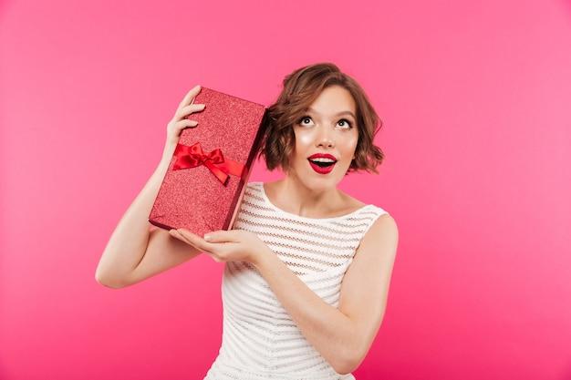 Портрет веселая девушка, одетая в платье, держа подарок