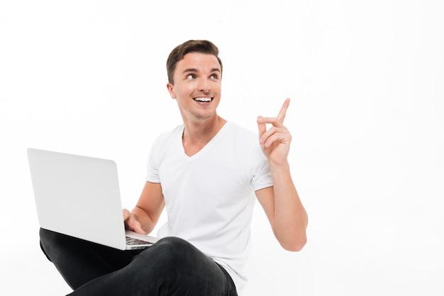 ラップトップコンピューターを保持している陽気なハンサムな男の肖像
