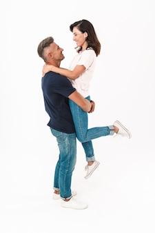 Портрет жизнерадостной позитивной взрослой влюбленной пары, изолированной над белой стеной, весело проводящей время.