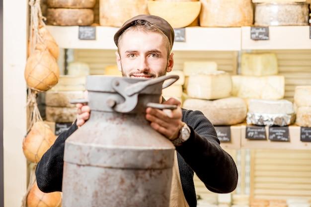 チーズショップに立っている大きな乳製品のバケツを持つチーズ売り手の肖像画