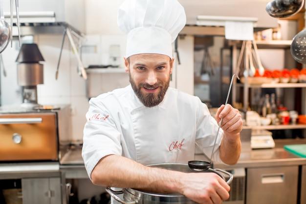 Портрет повара в униформе с большой плитой на кухне ресторана