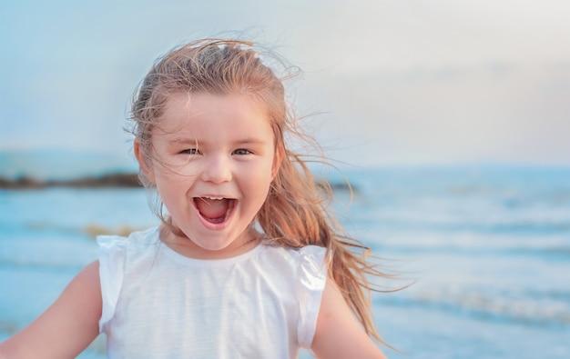 海で子供の肖像画。女の子は笑う