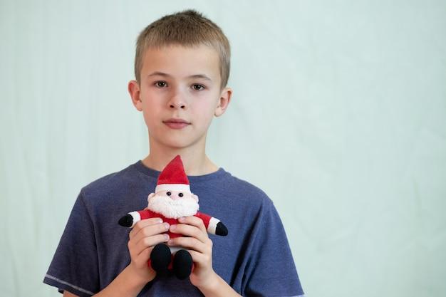 작은 산타 클로스 장난감을 가지고 노는 아이 소년의 초상화.