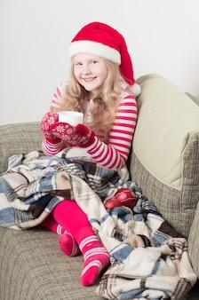 Портрет ребенка, пьющего горячий чай в шляпе санты