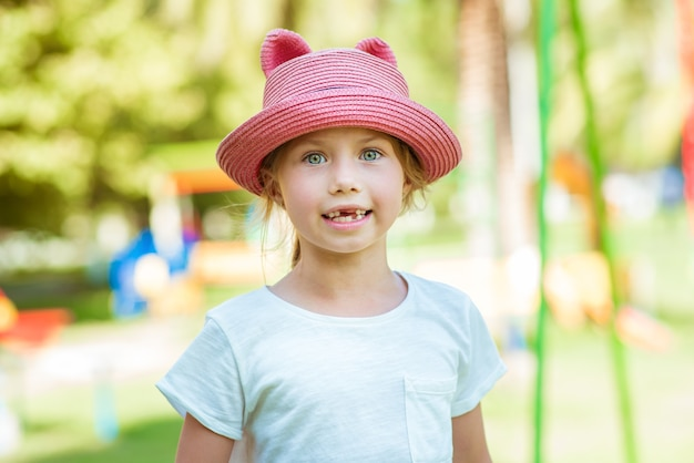 遊び場でピンクの帽子の子供の女の子の肖像画