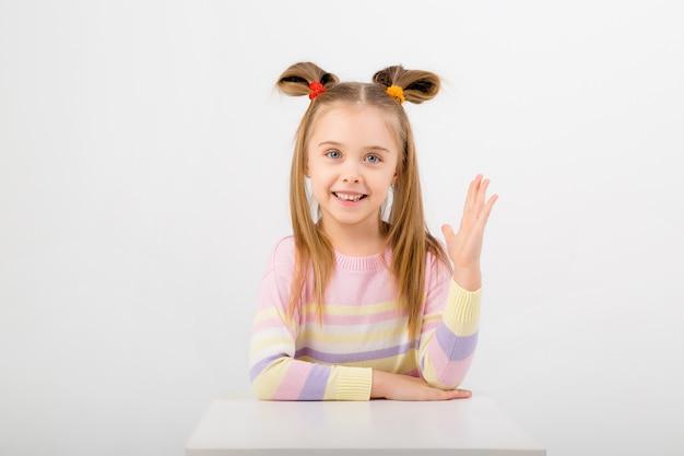 Портрет ребенка девушка сидит за столом и подняв руку. пробел, место для текста