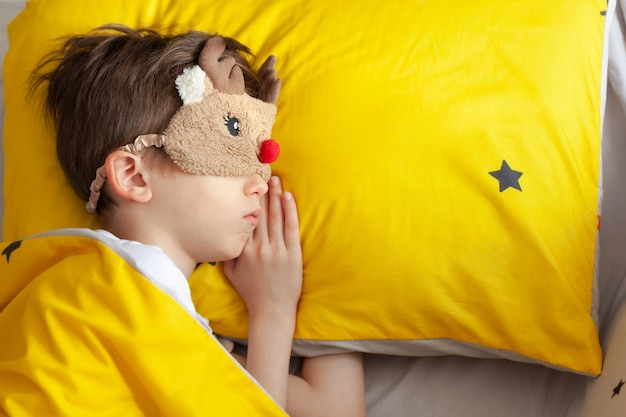 朝、黄色いベッドで寝ている睡眠マスクの子供の肖像画。