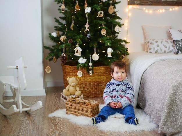 Портрет ребенка у новогодних украшений и елки.