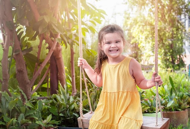 ブランコに乗る子供の肖像画。黄色いドレスを着た女の子が裏庭で時間を過ごす