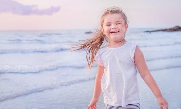 ビーチで子供の肖像画。日没の女の子