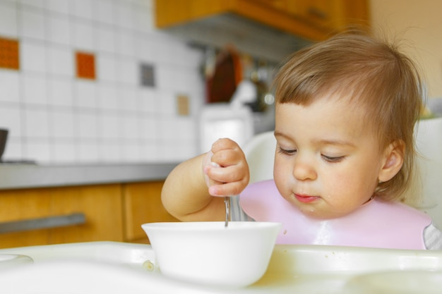 彼のスプーンで離乳食を食べる子供の肖像画。私の顔は食べ物でまみれて