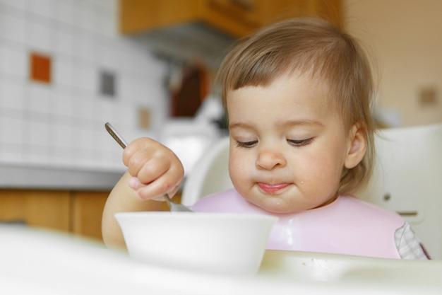 Портрет ребенка, который ест детское питание с его ложкой.