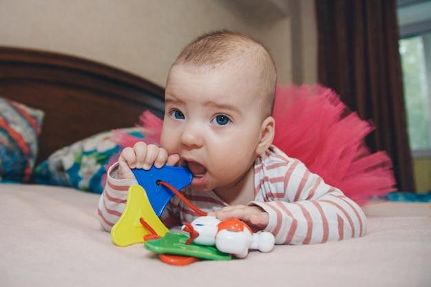 赤ちゃんのガラガラを持つ子供の肖像画。女の子が遊んでいます。細かい運動能力開発のコンセプト