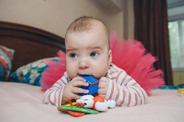 赤ちゃんのガラガラを持つ子供の肖像画。女の子が遊んでいます。細かい運動能力の開発、教育ゲーム、子供時代、子供の日、幼稚園copyspaceの概念