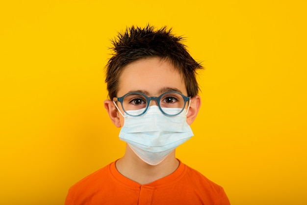 Портрет ребенка с маской для лица от коронавируса covid-19 на желтом