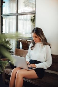 캐주얼 옷을 입은 집중적이고 진지한 아시아 여성의 초상화는 야외 벤치에서 노트북 작업을 하고 있습니다.