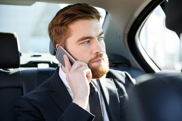 Портрет сконцентрированного бизнесмена говоря на мобильном телефоне