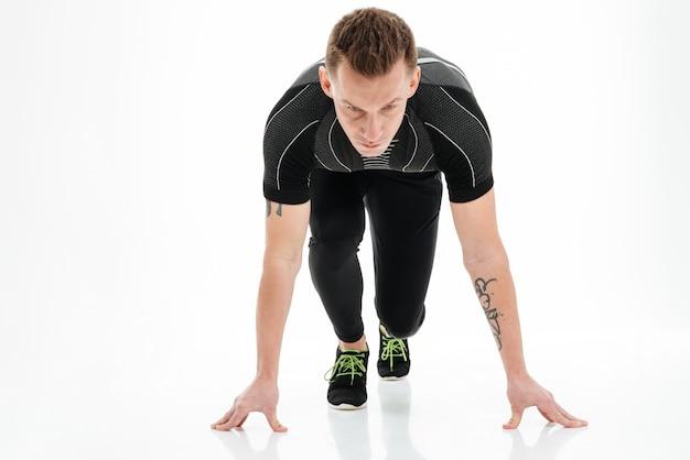 Портрет сосредоточенного мужского спринтера, готовящегося бежать