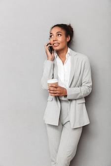 立っているスーツを着て、一杯のコーヒーを持って、携帯電話で話している自信を持ってアフリカのビジネス女性の肖像画