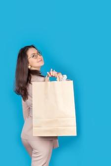 青い背景で隔離のバッグを保持している軽いスーツで自信を持ってビジネスの女の子の肖像画