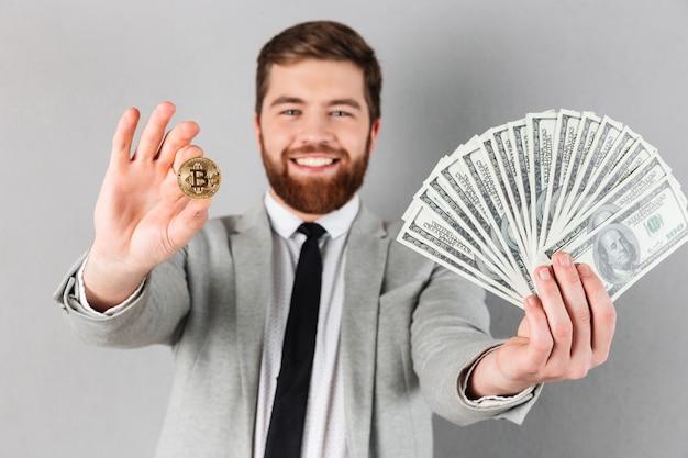 Портрет уверен бизнесмен, показывая биткойн