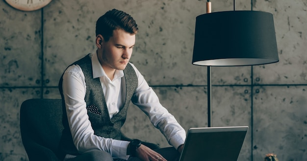 Портрет уверенно бизнесмена, работающего на ноутбуке в его офисе серьезно против серой стены.