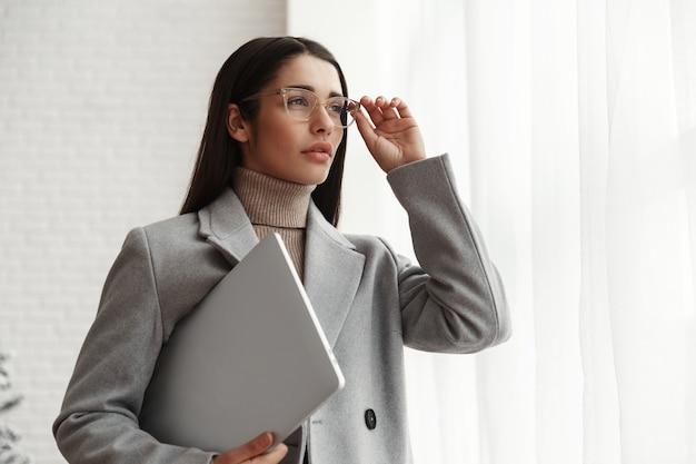 Портрет уверенно коммерсантки, стоящей внутри офисного здания с портативным компьютером.
