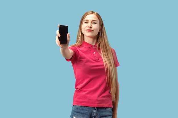 青い壁に分離された空白の画面の携帯電話を示す自信を持ってカジュアルな女の子の肖像画