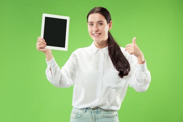緑の背景に分離されたノートパソコンの空白の画面を示す自信を持ってカジュアルな女の子の肖像画。