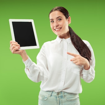 녹색 배경 위에 절연 노트북의 빈 화면을 보여주는 자신감 캐주얼 여자의 초상화.