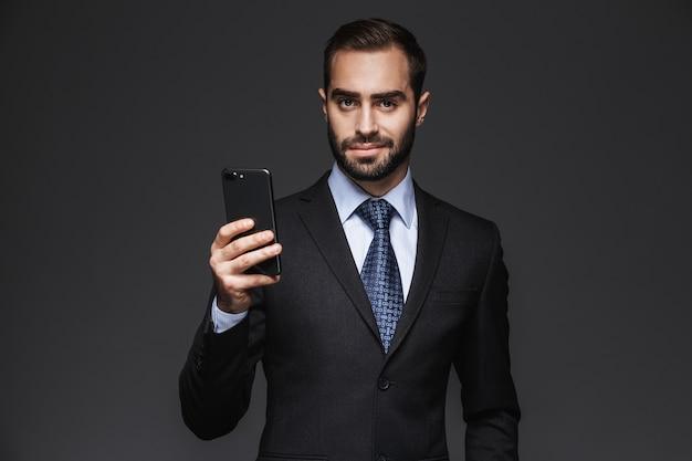 Портрет уверенно красивого бизнесмена в костюме, стоящего изолированно, с помощью мобильного телефона