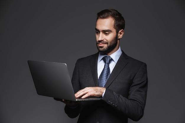 Портрет уверенно красивого бизнесмена в изолированном костюме, держащего портативный компьютер
