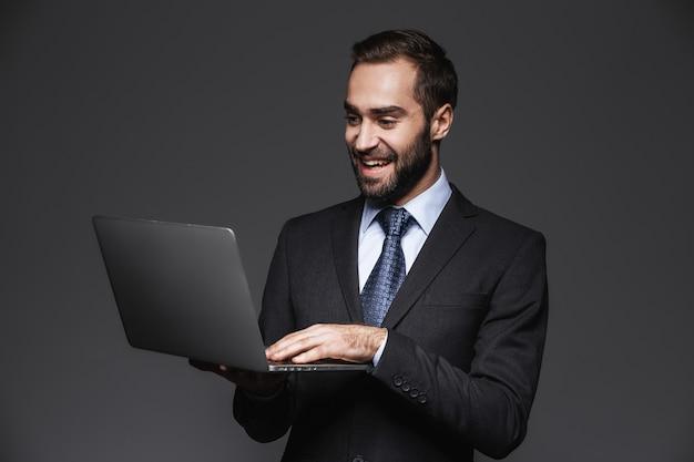 孤立したスーツを着て、ラップトップコンピューターを保持している自信を持ってハンサムなビジネスマンの肖像